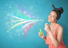 吹抽象五颜六色的泡影和线的美丽的女孩 免版税图库摄影