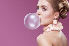 吹桃红色泡泡糖的美丽的白肤金发的妇女 方式纵向 库存图片