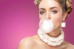 吹桃红色泡泡糖的美丽的白肤金发的妇女 方式纵向 库存照片