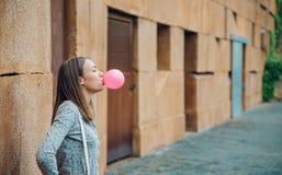 吹桃红色泡泡糖的年轻十几岁的女孩 图库摄影