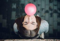 吹桃红色泡泡糖的年轻十几岁的女孩 库存图片