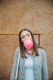 吹桃红色泡泡糖的年轻十几岁的女孩 免版税库存照片