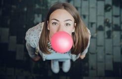 吹桃红色泡泡糖的年轻十几岁的女孩 免版税库存图片