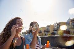 吹泡影的两个愉快的女孩 免版税库存图片