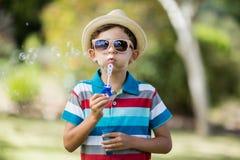 吹泡影的太阳镜的年轻男孩通过泡影鞭子 免版税库存照片