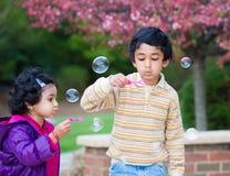 吹泡影的孩子在他们的围场 免版税库存照片