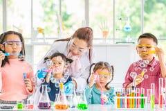 吹泡影的老师和学生在实验室 免版税库存照片