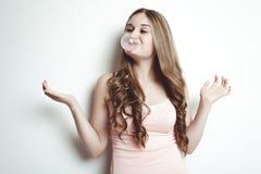 吹泡泡糖气球的白肤金发的少年女孩 免版税图库摄影
