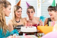 吹灭在她的生日蛋糕的妇女蜡烛,当庆祝时 免版税库存图片