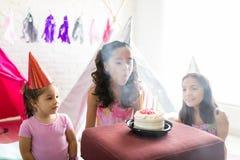 吹灭在生日蛋糕的女孩蜡烛由朋友 免版税库存图片