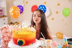 吹灭蜡烛的逗人喜爱的小女孩在她的生日 库存照片