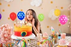 吹灭蜡烛的逗人喜爱的小女孩在她的生日 免版税库存图片