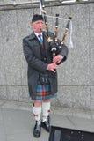 吹爱丁堡的吹风笛者他的管道 免版税库存图片