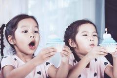吹生日杯形蛋糕的两个逗人喜爱的亚裔儿童女孩 免版税库存图片
