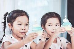 吹生日杯形蛋糕的两个逗人喜爱的亚裔儿童女孩 库存图片