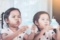 吹生日杯形蛋糕的两个逗人喜爱的亚裔儿童女孩 免版税库存照片