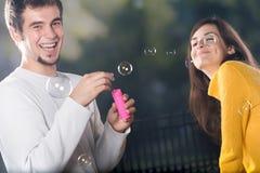 吹的泡影耦合户外微笑的年轻人 免版税库存图片