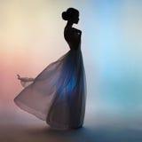 吹的礼服的剪影端庄的妇女 免版税库存照片