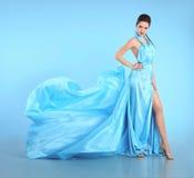 吹的蓝色礼服美丽的女孩 飞行褂子的,丝绸妇女 免版税库存图片