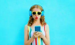 吹红色嘴唇的凉快的女孩拿着听到在无线耳机的音乐的电话在五颜六色的蓝色 免版税库存图片