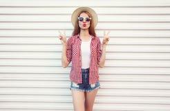 吹红色嘴唇的凉快的女孩送在夏天回合草帽,方格的衬衣,在白色墙壁上的短裤的甜空气亲吻 免版税库存图片