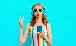吹红色嘴唇的画象凉快的女孩送听到在无线耳机的音乐的甜空气亲吻藏品电话在五颜六色 库存照片