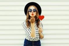 吹红色嘴唇的画象年轻女人送与红色心形的棒棒糖的甜空气亲吻在白色墙壁上的黑圆的帽子 免版税库存照片
