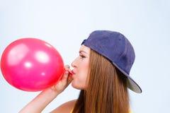 吹红色气球的青少年的女孩 免版税库存照片