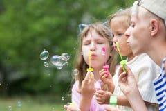 吹肥皂泡的孩子 免版税库存照片