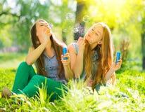 吹肥皂泡的秀丽女孩在春天公园 库存图片