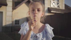 吹蒲公英和看照相机微笑的一相当逗人喜爱的女孩的画象 儿童消费时间 股票视频