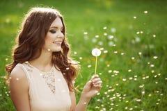 吹蒲公英的美丽的妇女 免版税图库摄影