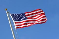 吹蓝旗信号天空风的美国人 免版税库存图片