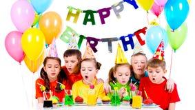 吹蜡烛的小组孩子在生日聚会 免版税库存图片