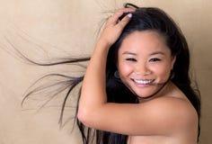 吹逗人喜爱的头发妇女的亚洲人新 图库摄影