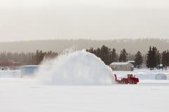 吹雪机在冬天风暴飞雪的清洁路 免版税库存图片