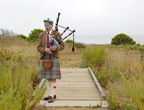 吹风笛者表面他的包括老 免版税图库摄影