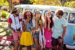 吹从泡影鞭子的小组朋友泡影在公园 免版税库存照片