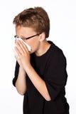 吹他的鼻子的一个十几岁的男孩被隔绝在白色 免版税库存图片