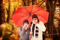 吹他们的鼻子的成熟夫妇的综合图象在伞下 免版税库存照片