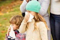 吹他们的鼻子的病的家庭 免版税图库摄影