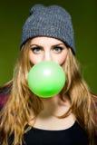 吹绿色bubblegum的美丽的少妇 免版税图库摄影