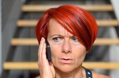 告诉严肃的红头发人的妇女某人电话的 免版税库存照片