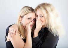 告诉女朋友愉快的秘密二个年轻人 免版税库存图片