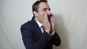 告诉年轻英俊的商人投入他的手对他的嘴和呼喊顾客 股票视频