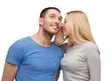 告诉微笑的女朋友男朋友秘密 免版税库存图片