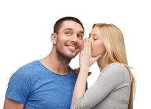 告诉微笑的女朋友男朋友秘密 图库摄影