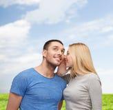告诉微笑的女朋友男朋友秘密 免版税库存照片