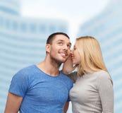 告诉微笑的女朋友男朋友秘密 库存图片