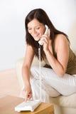 告诉拨号的家庭编号电话妇女 图库摄影